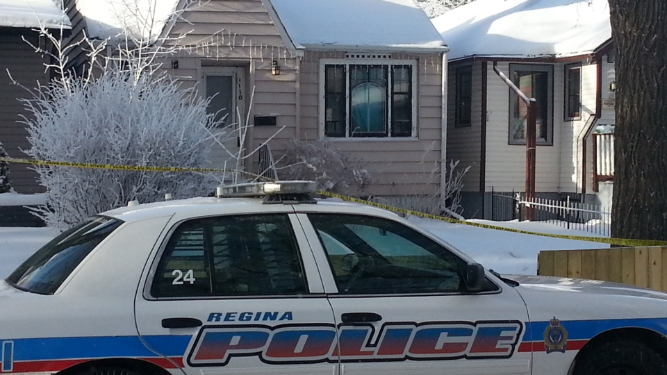 A Regina police cruiser and police tape is seen outside a house where the body of a missing woman was discovered last Friday.