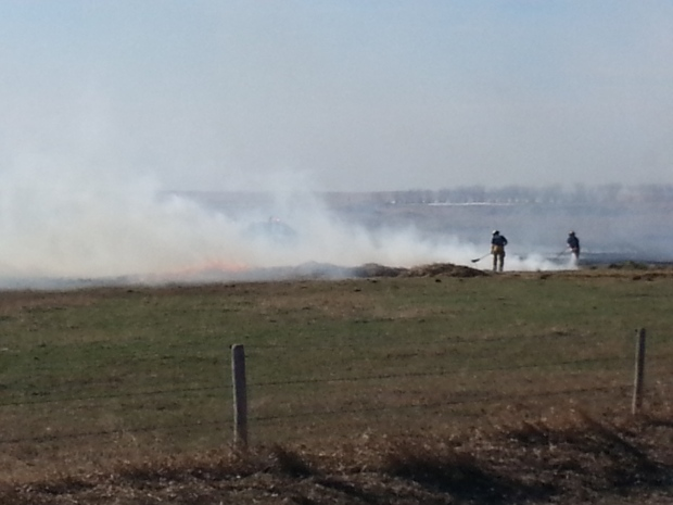Firefighters and volunteers work to extinguish a fire on a farm on Highway 6 north of Regina.