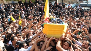 Lebanese mourners carry the coffin of Hezbollah fighter Hassan Faisal Shuker, 18, who was killed in a battle against Syrian rebels in the Syrian town of Qusair, during his funeral procession in his hometown of Nabi Sheet in the eastern Bekaa valley, Lebanon, Monday May 20, 2013. (AP)