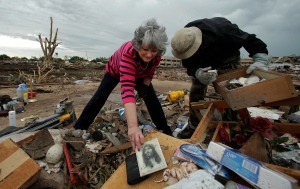 The day after a deadly storm ripped through the Oklahoma and Kansas, the search for survivors continues and residents begin to sift through the devastation. <br><br>Lea Bessinger salvages a picture of Jesus as she and her son Josh Bessinger sort through the rubble of the elder Bessinger&#39;s tornado-ravaged home in Moore, Okla., Tuesday, May 21, 2013. (AP / Charlie Riedel)