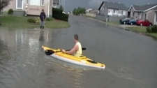 Tyler Dahlman kayaks down residential street Jenkins Drive after Saturday�s storm in Regina.