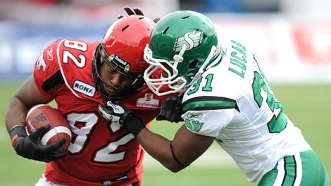 Calgary Stampeders' Nik Lewis, left, is stopped by Saskatchewan Roughriders' Sean Lucas during second half CFL acton in Calgary on Saturday Oct. 1, 2011. THE CANADIAN PRESS/Larry MacDougal