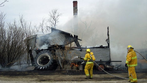 Firefighters battle a blaze at an unoccupied house at the Arm River Hutterite colony Thursday.