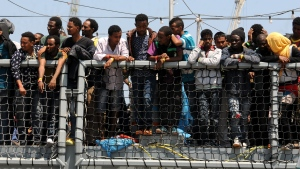Migrants wait to disembark from the German Navy ship Hessen at the Palermo harbor, Italy on June 7, 2015. European rescue boats are bringing thousands of migrants saved at sea to Italian ports, prompting center-right politicians to vow that their regions won't shelter any more of them. (AP / Alessandro Fucarini)