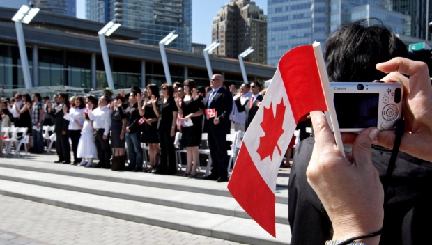 A woman takes a photograph while holding a Canadian flag as a group of 61 new Canadians take the oath of citizenship during a citizenship ceremony held as part of Canada Day celebrations in Vancouver, B.C., on Wednesday July 1, 2009. (Darryl Dyck / THE CANADIAN PRESS)