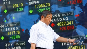 A man walks past an electronic stock indicator of a securities firm in Tokyo, Monday, Sept. 14, 2015. (AP / Shizuo Kambayashi)