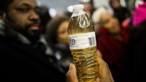 Pastor David Bullock holds up a bottle of Flint water as Michigan State Police hold a barrier to keep protestors out of the Romney Building, where Gov. Rick Snyder's office resides in Lansing, Mich. on Thursday, Jan. 14, 2016. (Jake May / The Flint Journal-MLive.com)