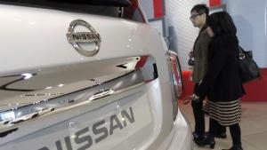 Visitors walk past a Nissan car at its global headquarters in Yokohama, near Tokyo on Wednesday, Feb. 10, 2016. (AP / Eugene Hoshiko)