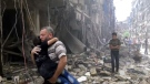 In this image made from video and posted online from Validated UGC, a man carries a child after airstrikes hit Aleppo, Syria, Thursday, April 28, 2016.  (Validated UGC / AP video)