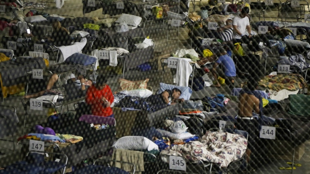 Evacuees from the Fort McMurray wildfires rest on a hockey rink at the evacuation centre in Lac la Biche, Alta. on Thursday, May 5, 2016. (Jeff McIntosh / THE CANADIAN PRESS)