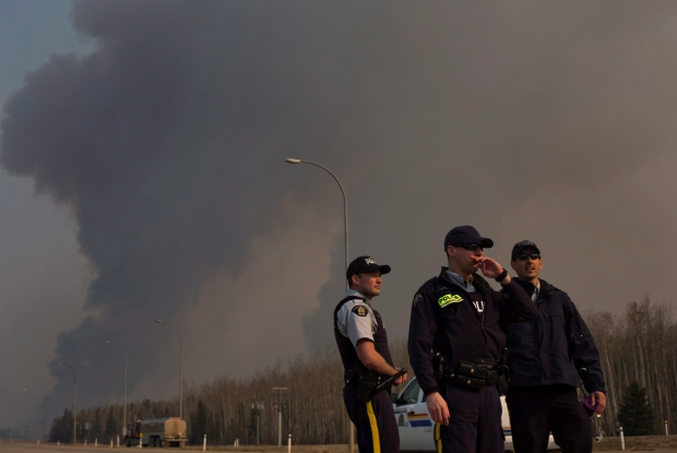 Police man a roadblock as smoke billows in the background near a wildfire in Fort McMurray, Alta., on Friday, May 6, 2016. (Jason Franson / THE CANADIAN PRESS)