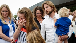 Collet Stephan, second from left, wipes away a tear as she and her husband David Stephan arrive at the courthouse with their children in Lethbridge, Alta., Friday, June 24, 2016. (Jeff McIntosh / THE CANADIAN PRESS)