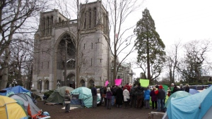 People demonstrate at the homeless camp in Victoria in a January 11, 2015, file photo. The British Columbia government says fire, crime and sanitary conditions at a homeless camp outside the courthouse in Victoria have degenerated since March when the province originally applied for a court injunction to shut it down. (THE CANADIAN PRESS/File)