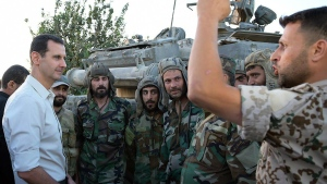 Syrian President Bashar Assad, left, speaks with Syrian troops during his visit to the front line in the Damascus suburb of Marj al-Sultan, Syria on Sunday, June 26, 2016. (SANA)