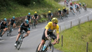 Britain's Chris Froome, wearing the overall leader's yellow jersey, leads the pack as they speed downhill during the nineteenth stage of the Tour de France cycling race over 146 kilometers (90.7 miles) with start in Albertville and finish in Saint-Gervais Mont Blanc, France, Friday, July 22, 2016. (AP Photo/Christophe Ena)