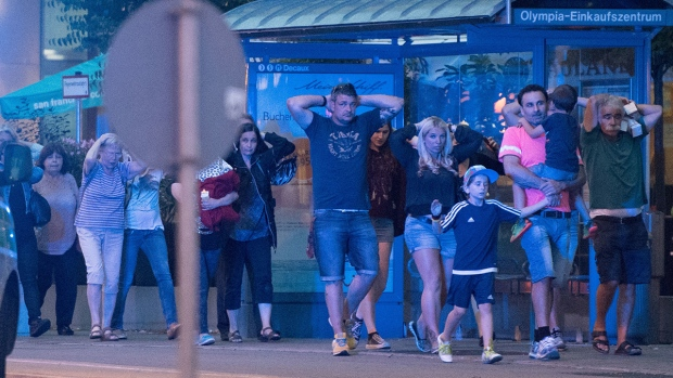 People leave the Olympia mall in Munich, southern Germany, Friday, July 22, 2016 after several people have been killed in a shooting. (AP / Sebastian Widmann)