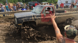 Spectators cheer as a pickup truck splashes through mud at an event formerly called the Redneck Olympics on Saturday, July 30, 2016, in Hebron, Maine. (David Sharp/AP Photo)