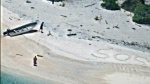 """A pair of stranded mariners signal for help by writing """"SOS"""" in the sand as a U.S. Navy P-8A Poseidon aircraft crew from Patrol Squadron (VP) 8 flies over in support of a Coast Guard search and rescue mission. (U.S. Navy / Handout)"""