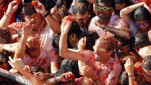 """Crowds of people throw tomatoes at each other, during the annual """"Tomatina"""", tomato fight fiesta, in the village of Bunol, 50 kilometres outside Valencia, Spain, Wednesday, Aug. 31, 2016. (AP / Alberto Saiz)"""