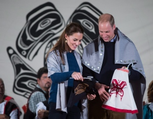 Draped in traditional First Nation blankets, Britain's Prince William, the Duke of Cambridge, and Kate, the Duchess of Cambridge, hold vests they were presented with for Prince George and Princess Charlotte during a welcoming ceremony at the Heiltsuk First Nation in the remote community of Bella Bella, B.C., on Monday September 26, 2016. (THE CANADIAN PRESS/Darryl Dyck)