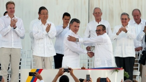 Colombia's President Juan Manuel Santos, front left, and the top commander of the Revolutionary Armed Forces of Colombia, FARC, Rodrigo Londono, known by the alias Timochenko, shake hands after signing the peace agreement between Colombia's government and the FARC to end over 50 years of conflict in Cartagena, Colombia on Sept. 26, 2016. (AP / Fernando Vergara)