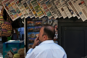 This is a Sunday, July 12, 2015 file photo of a man as he smokes a cigarette as he looks at daily newspapers displayed at a kiosk in central Athens. (AP Photo/Petros Karadjias, File)