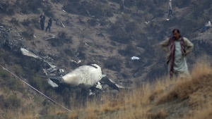 A Pakistan villager stands at the site of plane crash as investigation is in progress in Gug near Havelian, Pakistan on Thursday, Dec. 8, 2016. (AP / B.K. Bangash)