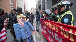 Anti-Trump protesters stop in front of the United States consulate during a demonstration Friday, January 20, 2017 in Montreal. (THE CANADIAN PRESS / Ryan Remiorz)