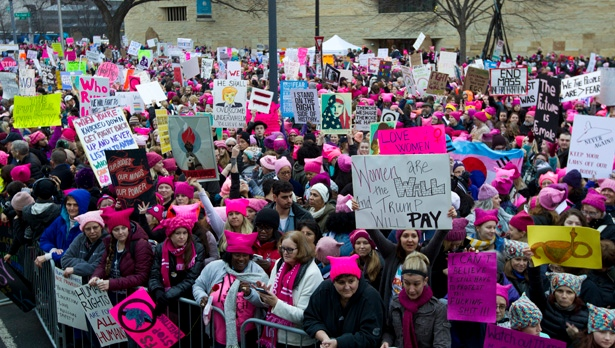 Women with bright pink hats and signs begin to gather early and are set to make their voices heard on the first full day of Donald Trump's presidency, Saturday, Jan. 21, 2017 in Washington. ( AP Photo/Jose Luis Magana)