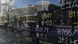 A woman is reflected on an electronic stock indicator of a securities firm in Tokyo, Tuesday, Jan. 24, 2017. (AP / Shizuo Kambayashi)